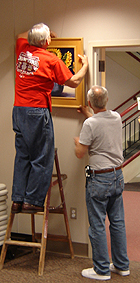 Paul Miller and Tom Mayer hanging the artworks